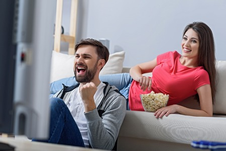 Football and popcorn time. Shot of couple sitting on their sofa and eating popcorn while watching football match 版權商用圖片