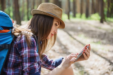 seriousness: Cheerful female tourist is using mobile phone navigator. She is sitting in forest and looking at screen with seriousness Stock Photo