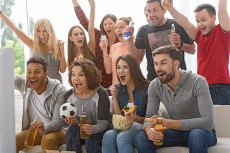 rooting: Finally we have got first goal. Group of happy friends rooting for their soccer team on TV and celebrating goal