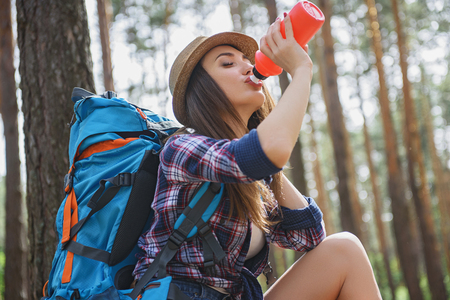 Thirsty young woman is drinking water from bottle in forest. Her eyes are closed with pleasure Stock Photo