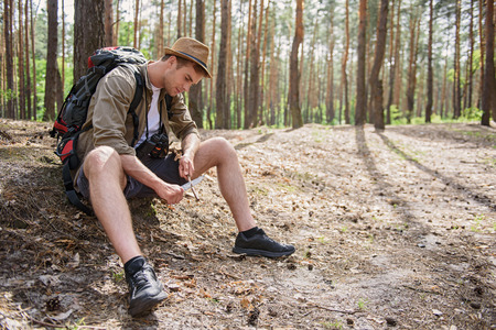 whittle: Skillful young man is using a knife to whittle a stick out with concentration. He is sitting on ground in forest Stock Photo