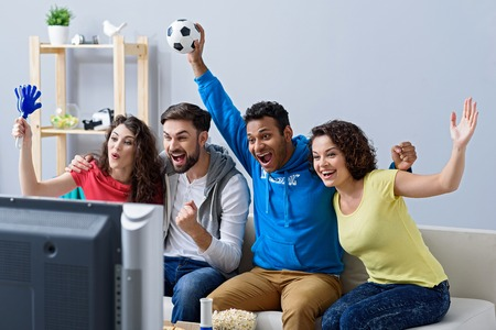 hurray: Sunday sports. Group of happy sports fans watching game on TV at home and holding soccer attributes Stock Photo