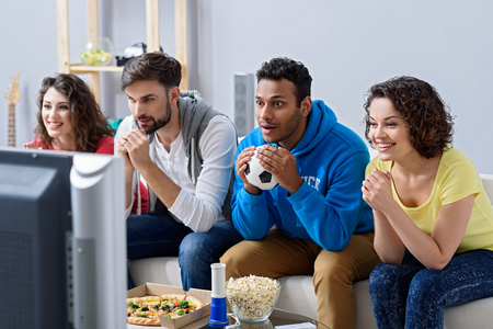 hurray: Real emotions unite friends. Sports friends fans cheering and celebrating exciting game on television, sitting on sofa at home Stock Photo