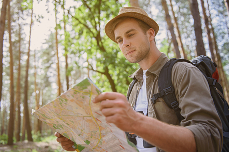 seriousness: Cheerful male tourist is making journey in forest. He is standing and looking at map with seriousness