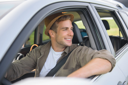 adventurer: Cheerful young man is making trip by car. He is sitting at steering wheel and enjoying nature. Adventurer is smiling
