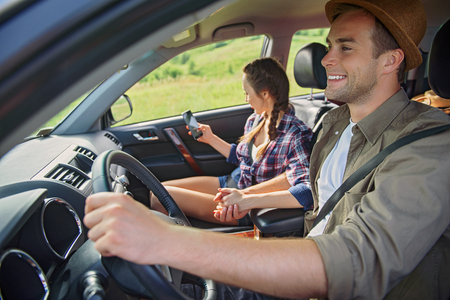 countryside loving: Happy loving couple is making trip in countryside. They are sitting in car and holding hands. Man is smiling. Woman is using mobile phone Stock Photo