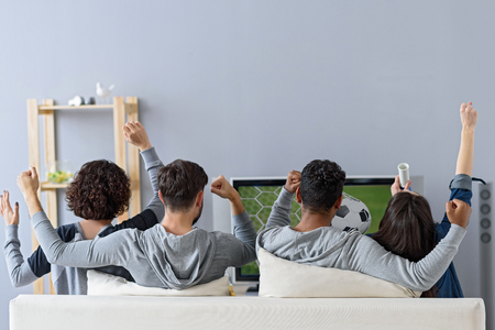 Devoted fans. Rear view of four friends watching game of their favorite team and celebrating goal