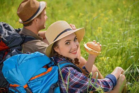 Cheerful tourists are resting on meadow. They are sitting on grass and eating sandwich. Woman is looking at camera and smiling