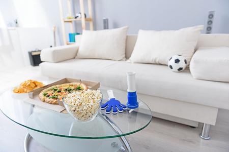 Alles klaar voor het bekijken van voetbalwedstrijden. Bijgesneden foto van de woonkamer met witte sofa en pizza, chips, popcorn op koffietafel