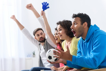 What intriguing game. Multi racial group of sports fans watching football on TV, sitting on sofa at home with soccer attributes