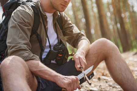 whittle: Male traveler is using knife to whittle a stick. Man is sitting in forest