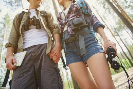 Happy tourists are making romantic journey in forest. They are standing and holding hands. Man is looking at woman with love and smiling
