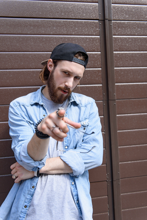 seriousness: You. Confident hipster man is pointing finger at camera with seriousness. He is standing and leaning on wall