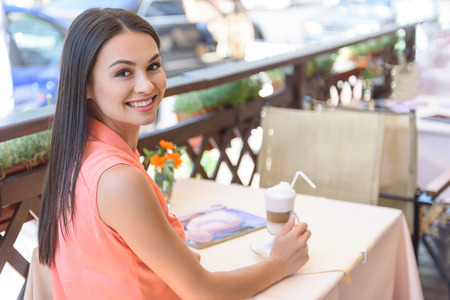 Cheerful young woman is resting in cafe. She is holding cup of latte and smiling