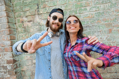 Pretty couple is showing peace sign and smiling. They are standing and embracing. Man and woman are wearing sunglasses Stock Photo