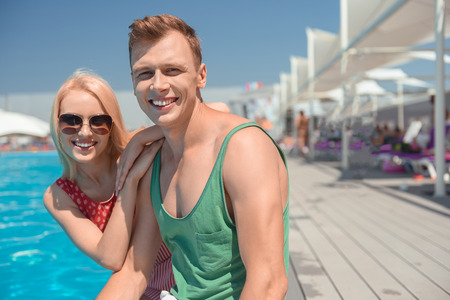 Young loving couple is enjoying vacation near water. They are sitting and embracing. Man and woman are looking at camera and smiling Stock Photo