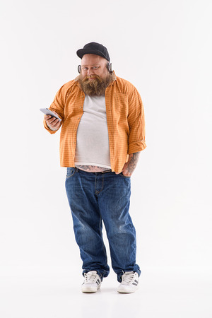 hick: Bearded fat male hipster is listening to music and smiling. He is standing and holding smartphone. Isolated