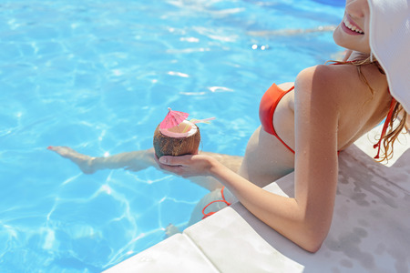 Joyful young girl is swimming in pool and relaxing. She is drinking cocktail and smiling Stock Photo