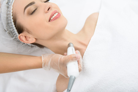 cosmetician: Joyful young woman is getting laser skin treatment at spa salon. She is lying and smiling. Beautician is touching equipment to her neck