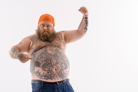 I am very strong. Fat bearded man is pointing finger at his big abdomen with proud. He is raising arm and showing muscle. Isolated and copy space in right side Banco de Imagens
