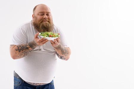 Hombre gordo está sosteniendo plato de ensalada y olerlo con el placer. Él está de pie con los ojos cerrados. espacio aislado y la copia en el lado izquierdo