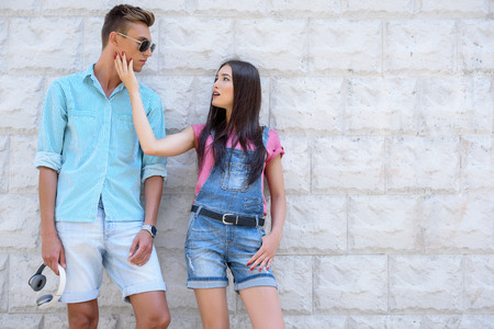 gentleness: Young woman is touching male face with gentleness. Man is standing and looking at his girlfriend with love