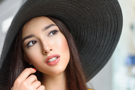 sunhat: Attractive young girl is looking forward with desire. She is standing in large sunhat