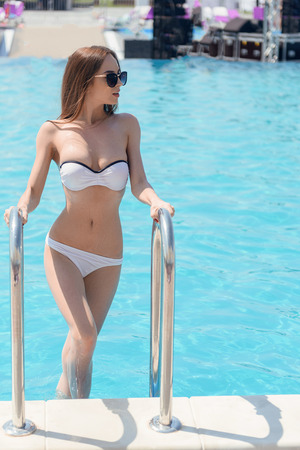fun in the sun: Attractive young woman is standing on staircase in swimming pool. She is looking aside with passion