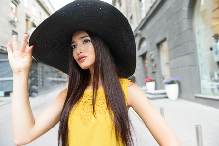 elegantly: Stylish young woman is having walk in city. She is looking forward with interest. Lady is standing and touching hat elegantly