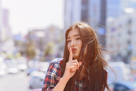 secretly: Hush-hush. Attractive young woman is raising finger to lips secretly. She is standing in city Stock Photo