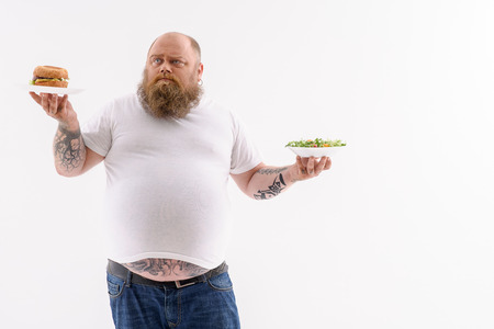 met: What to choose. Pensive thick man is making choice between healthy and unhealthy food. He is standing and holding plates. Isolated Stock Photo