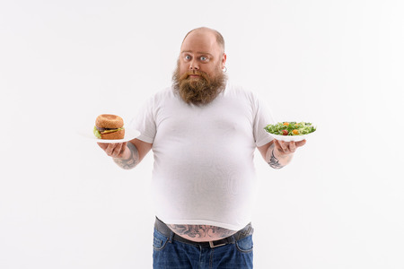 Puzzled fat man is choosing between sandwich and salad. He is standing and looking at camera pensively. Isolated