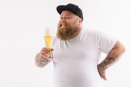 Joyful fat man is drinking beer and smiling. His eyes are closed with pleasure. Isolated and copy space in left side Banco de Imagens