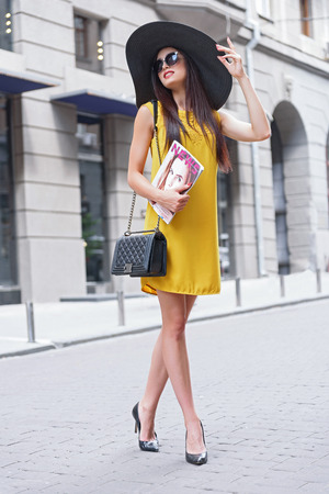 fashion magazine: Stylish young woman is walking in city. She is holding fashion magazine and smiling. Lady is standing and touching her hat elegantly