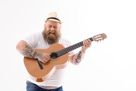 Inspired fat guitarist is preforming song with passion. He is standing and singing. Isolated