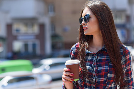 Confident young woman is drinking coffee on street. She is standing and loosing aside thoughtfully