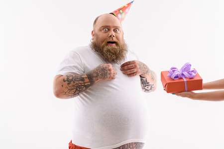 surprise box: Fat man is receiving gift box. He is standing and looking at camera with surprise. Man is wearing birthday cone. Isolated Stock Photo