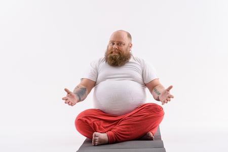 Froher dicker Mann bereitet sich auf Meditation vor. Er sitzt und entspannt sich. Mann schaut Kamera mit Einladung an. Isoliert Standard-Bild