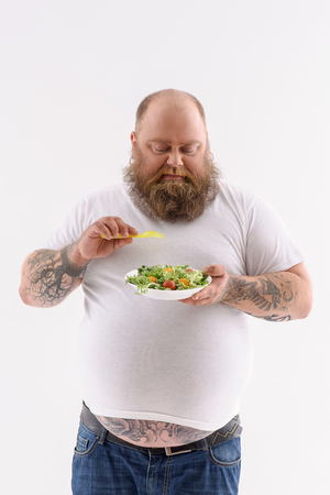 Fat bearded man is standing and eating salad. He is looking at plate with disgust. Isolated