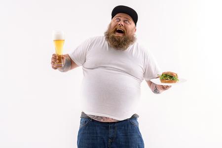 うれしそうなデブ男はビールとサンドイッチのガラスを保持しています。彼はありがたいことに見上げると、笑っています。分離されました。 写真素材