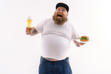 Joyful fat man is holding glass of beer and sandwich. He is looking up thankfully and laughing. Isolated Banco de Imagens