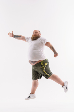 Fat man is exercising. He is stretching arm sideways and looking at camera with shock. Isolated