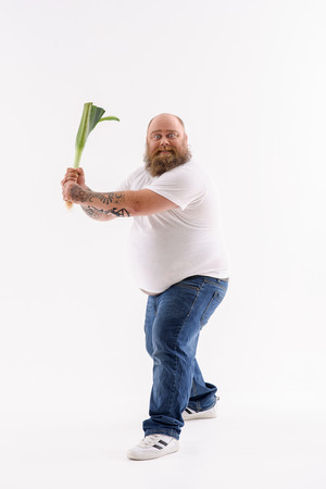 Fat bearded man is holding leek. He is standing in feedback position. Guy is looking at camera with preparation. Isolated Stock Photo
