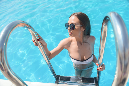 going out: Attractive young woman is going out from swimming pool. She is looking aside with joy Stock Photo