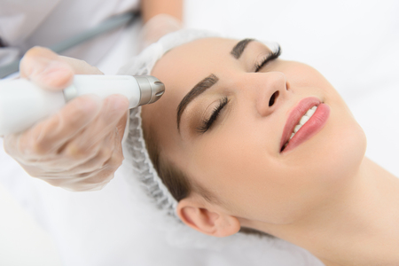 stimulating: Close up of young girl having stimulating facial treatment at professional clinic. She is smiling with closed eyes Stock Photo