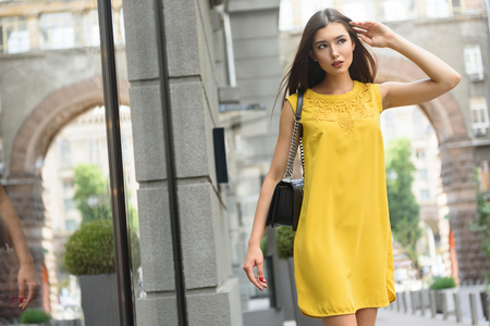 Attractive young woman is walking in city with relaxation. She is touching her hair and looking forward with interest Stock Photo