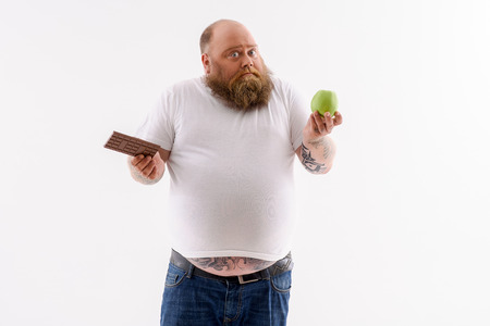 hesitation: Thick bearded man is choosing between apple and chocolate. He is standing and looking at camera with hesitation. Isolated