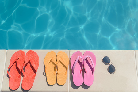 swimming shoes: Three pairs of flip flop shoes and sunglasses near swimming pool