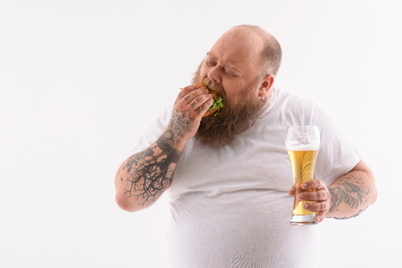 Thick bearded man is eating burger with greed. He is standing and holding glass of beer. Isolated
