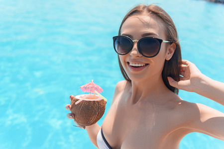 Joyful young woman is relaxing near blue water pool. She is touching her hair flirtingly and smiling. Lady is drinking coconut cocktail